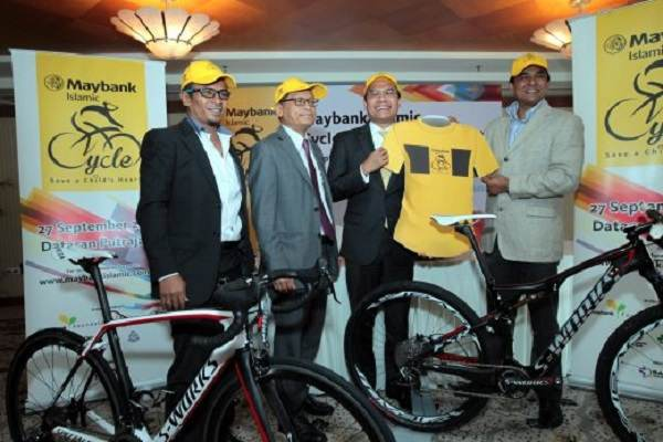 KUALA LUMPUR 19 SEPTEMBER 2014. M.Kumaresan (right) and CEO Maybank Iaslamic Berhad Muzaffar Hisham (second right) holds the event T'Shirt looks on EX Cycelist Musairi Musa (left) and CEO Institut Jantung Negara Datuk Dr.Mohd Azhari Yakub (second left) at Maybank Islamic Cycle